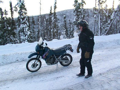 2/15/06 - Mile 42 or so on the Dalton Hwy. - taking a look at the bike, and getting off the highway to let trucks go on by. With these tires, and not studs in them, the bike was sliding almost constantly.  Stopping was better done by dragging my feet.
