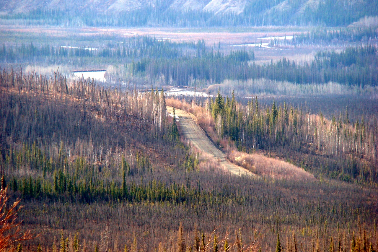 5/11/08 5:06 PM - Hess Creek wends its sinuous path through the flat valley floor, while nearer, the old roadway can be seen where it levels off to join the existing highway.