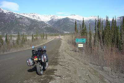 "Mile 188.4 - This is what the traveler will see (minus the KLR, of course) approaching the turn-off to Wiseman.  Shortly after crossing Minnie Creek, the road crosses the bridge marked ""Middle Fork Koyukuk River #1"", and the ""Wiseman Street"" sign is on the left.  From there it is a twisty 3 miles to the townsite of Wiseman."