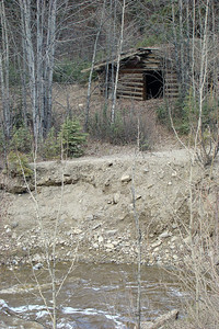 An abandoned log cabin on the west side of the highway, next to Gold Creek at MP197.