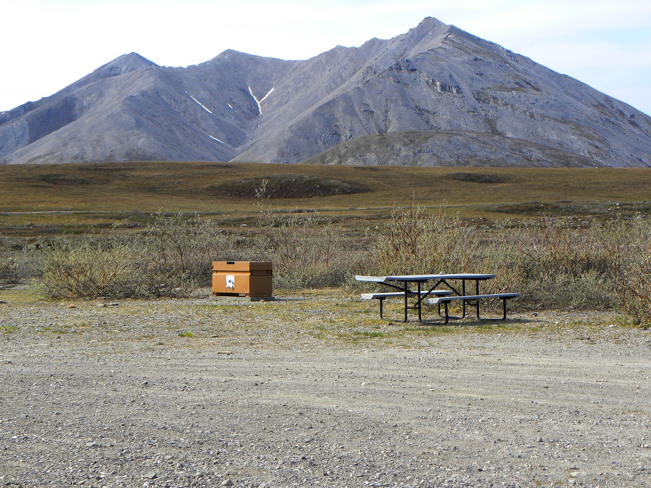 One of the picnic tables and the food locker.