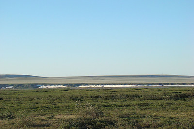 7/4/08 10:50 PM - From Mile 378, the view across the tundra to the south end of the Franklin Bluffs area.  Even with the warm temperatures, snow that drifted against the bluffs remains on the far side of the Sag River.