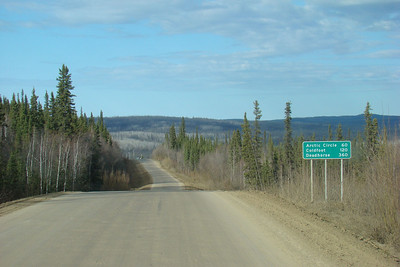Around Mile 55, with the lightposts on the Yukon River bridge visible just over the last hump in the road.