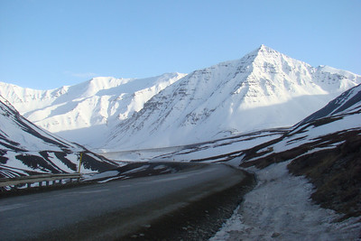 An evening shot of the Atigun valley, with the road ascending toward the summit of the pass apparent at the bottom of the mountain in the lower center of the photo.
