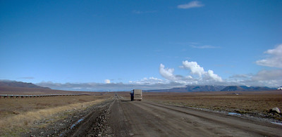 A lonely road?  Not any more.  Here, a muddy tour bus continues north toward Deadhorse with a load of visitors, who will return home far more knowledgeable regarding the oilfields surrounding Prudhoe Bay.