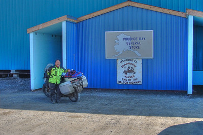 July 1, 2010:  Dean Tanji stands next to the sign, now located on the outside of the Arctic entry to the general store/post office/gift shop/NAPA store.