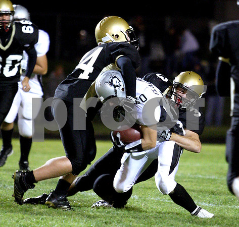 Chronicle photo KATE WEBER<br /> Tom Hensley and Kevin Sabock of Sycamore work together to take down a Kaneland offensive player Friday night at Sycamore High School.