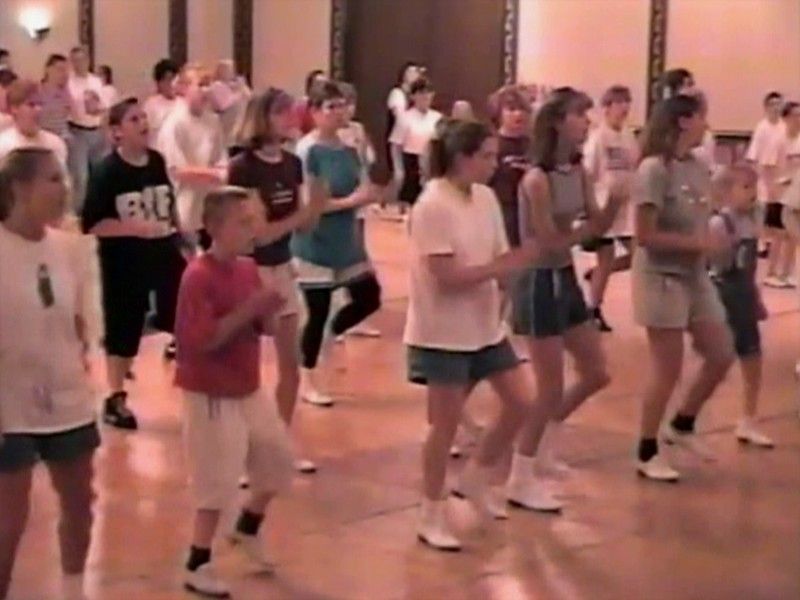 "Video Archive Clip 1998 (May 23) - Yaden Clogging - Julie (age 44, 3rd row in blue top/black tights), Jacob (age 13, 3rd row in black shirt/shorts) & Steven (age 10, front row in red shirt/white shorts) dance the ""Everybody"" routine by instructor Jeff Driggs - Memorial Day Weekend Clogging Workshop - Columbus, OH - Clogging Memoirs Series (2 min 53 sec)"