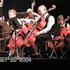 Video Archive Clip 2004 (Oct) - Yaden, Steven R. - Age 16 - From football practice to chamber orchestra - Following football practice, Steven plays cello in a concert by the TVHS Chamber Orchestra - Bob Kreutz, Orchestra Director - Thompson Valley High School Auditorium - Loveland, CO - Original VHS Series (17 min 30 sec)<br /> <br /> Note from Dad:<br /> <br /> I wonder how many fullbacks have this skill set in their repertoire?<br /> <br /> Julie and I remember this Wednesday night well. Thompson Valley had a big football game coming up on Friday night, and coach kept the players on the practice field late that Wednesday. <br /> <br /> Steve was released from practice 15 minutes prior to the concert. Of course, all orchestra members were supposed to arrive 30 minutes prior to a concert or you weren't allowed to play. But then football coaches don't seem to have much empathy for the musical types. Luckily, the music director Bob Kreutz was a big football fan.<br /> <br /> Anyway, Julie hurried Steve's instrument to the practice field and I remember other parents commenting about what a remarkable sight it was to see a football player running across the school parking lot in cleats and pads with a cello tucked under his arm! Steve made it just in time to throw off his uniform back stage, jump into his tux, and step onto the stage. You'll notice he didn't even have time to change his socks or tuck in his shirt!<br /> <br /> I know the football practice that afternoon was exhausting. How Steve managed to maneuver his fingers and arms that night is beyond me.