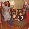 Julie Yaden (sitting in chair) - 1978 (Dec) - Age 24 - With Danny (standing center, age 8 mos) during Christmastime visit at the Selah farmhouse - Also in picture are Danny's Great Aunts Evelyn (cut off, far left) and Harriett (far right), as well as 2nd cousin Allen (sitting on footstool) - Selah, WA