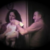 Julie Yaden - 1980 (February) - Age 25 - Holding baby Nicole Owen with Dave Yaden, Sr. (age 59) at the Selah farmhouse - Selah, WA (Captured from 8mm film)