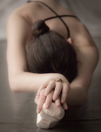 A dancer stretches during an idle moment in a photo shoot.