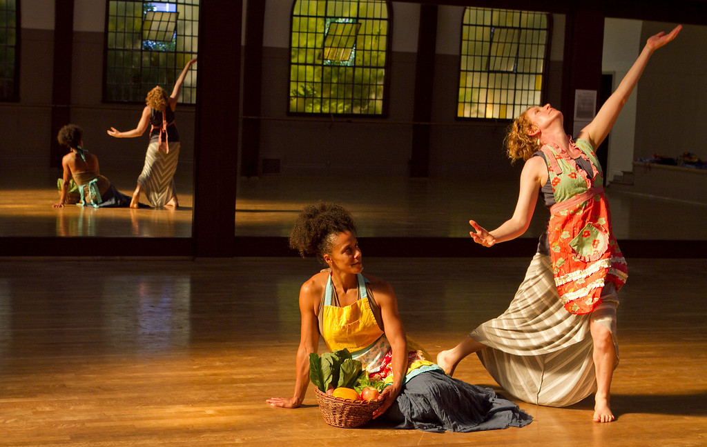 """Amara Tabor-Smith holds a basket of vegetables as Lisa Wymore dances at the UC Bancroft Dance Studio in Berkeley, Calif., on Friday, August 24th,  2012. They are holding a dance work shop called """"From the Field to the Table"""" that involves food and dance."""