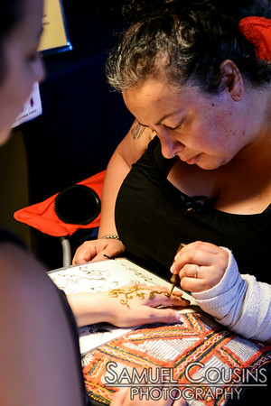 Maria O'Connor, of Ancient Fire Henna, painting a henna design onto a hand.