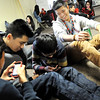 Tenzin Yeshi Paichang, right, laughs with Tenzin Chime, far left, brother Sonam Paichang, middle left, and Ngawang Lobsang, middle right, during a break from practice on their iphones. (Pioneer Press; Sherri LaRose-Chiglo)