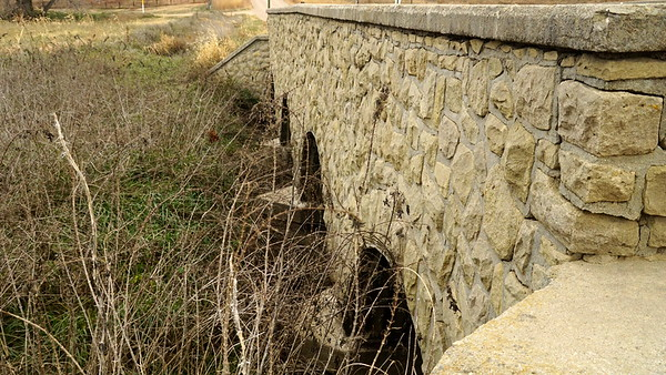 Four span stone arch bridge with steel culverts over a branch of the South Fork Prairie Dog Creek.