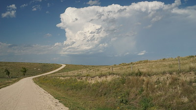 Road 3 winding thru hills in northwest Rawlins County. Thunderstorm in distance.
