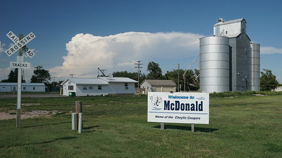 McDonald town welcome sign, Railroad, Grain Elevator and storm clouds in the distance.