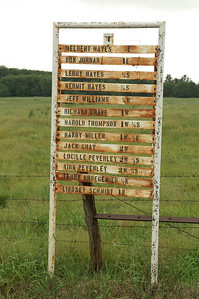 Sign with local farmer's names and distance to their farms