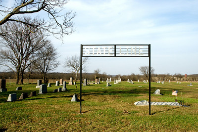 State Line Cemetery. (Notice the reflection of the sign on the flat tombstone below it)