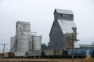 Older grain elevators and parked railroad cars in Tribune