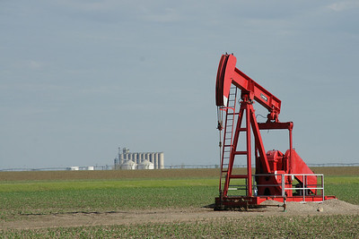 Bright red oil pump - southeast Haskell County. Sublette elevator in background