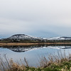 Snowey Benwisken and Benbulben Mountain with a still lake in the foreground and a perfect reflection.