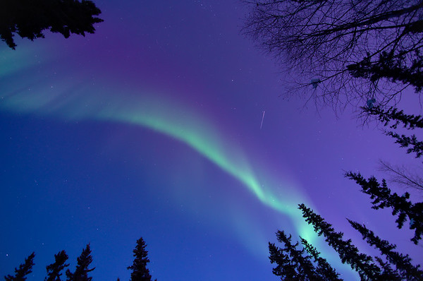 A satellite passes by as the aurora comes out, brilliantly, during twilight.