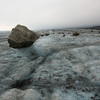 The rocks to a good job at insulating the ice beneath while the ice around them melts. Eventually they fall over.