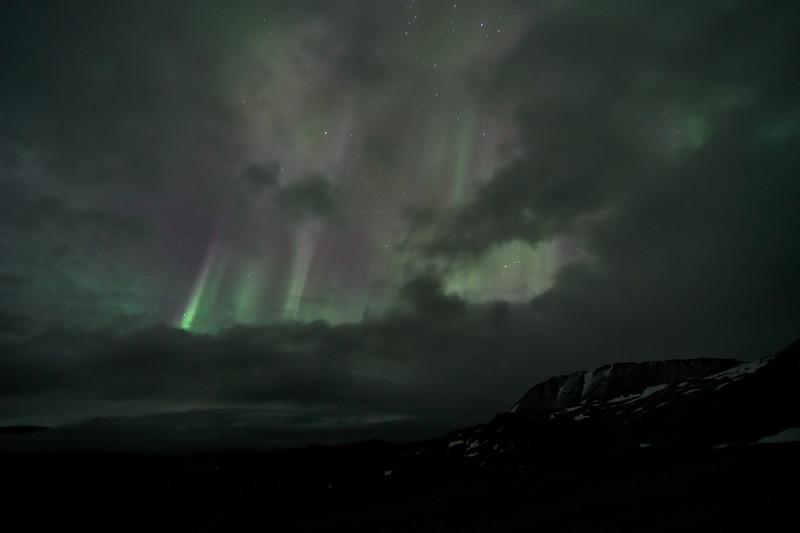 Aurora borealis through the clouds taken in the Rainbow Basin in the Alaska Range