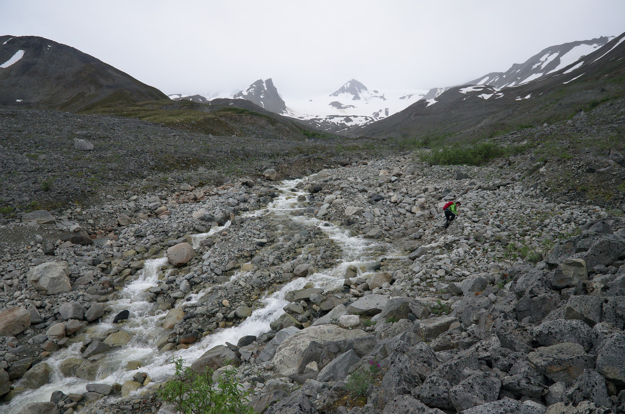 Person trying to find a safe place to cross a stream near the Canwell Glacier
