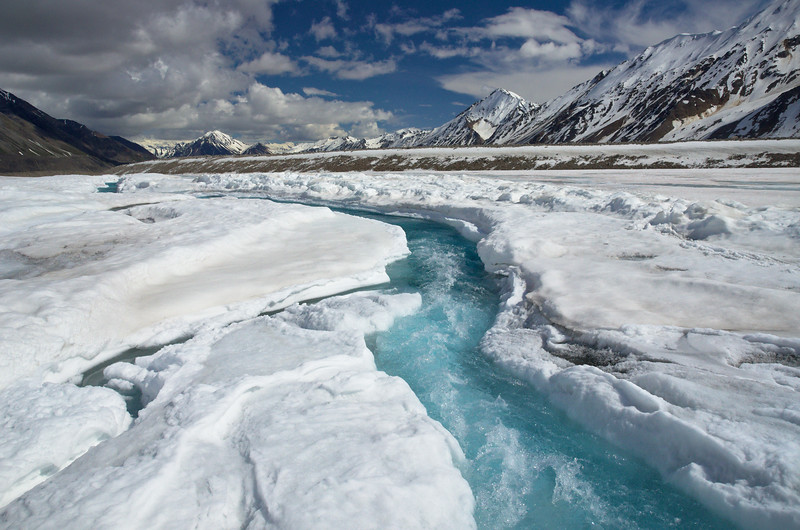 On the Black Rapids Glacier in the Eastern Alaska Range. Eventually the slushy blue streaks in the snow from a few days before this gave way to water channels in the ice beneath the surface. Sometimes they find old channels from previous years, sometimes they don't. In the summer of 2014 we spent two weeks camped on the glacier and had to cross many of these streams. It was still early in the melt season which meant that there weren't any moulins yet to drain the water for the surface. This meant that to get across the glacier we had to jump over many of these streams, a handful of which were quite wide. It was definitely a trip that was difficult on my knees!