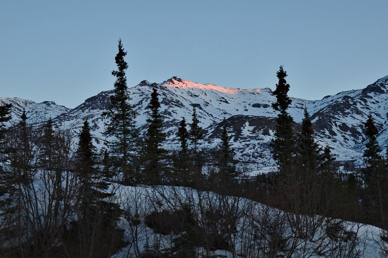 First light hits the top of the peaks north of the Park Road.