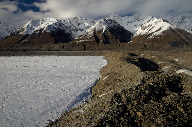 Snowline descends in the Alaska Range in early September. Landslide debris on the Black Rapids Glacier.