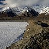 Snowline descends in the Alaska Range in early September. Landslide debris on the Black Rapids Glacier.