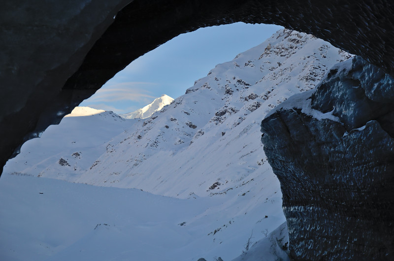 Looking at White Princess in the Alaska Range through an ice cave in the Castner Glacier.