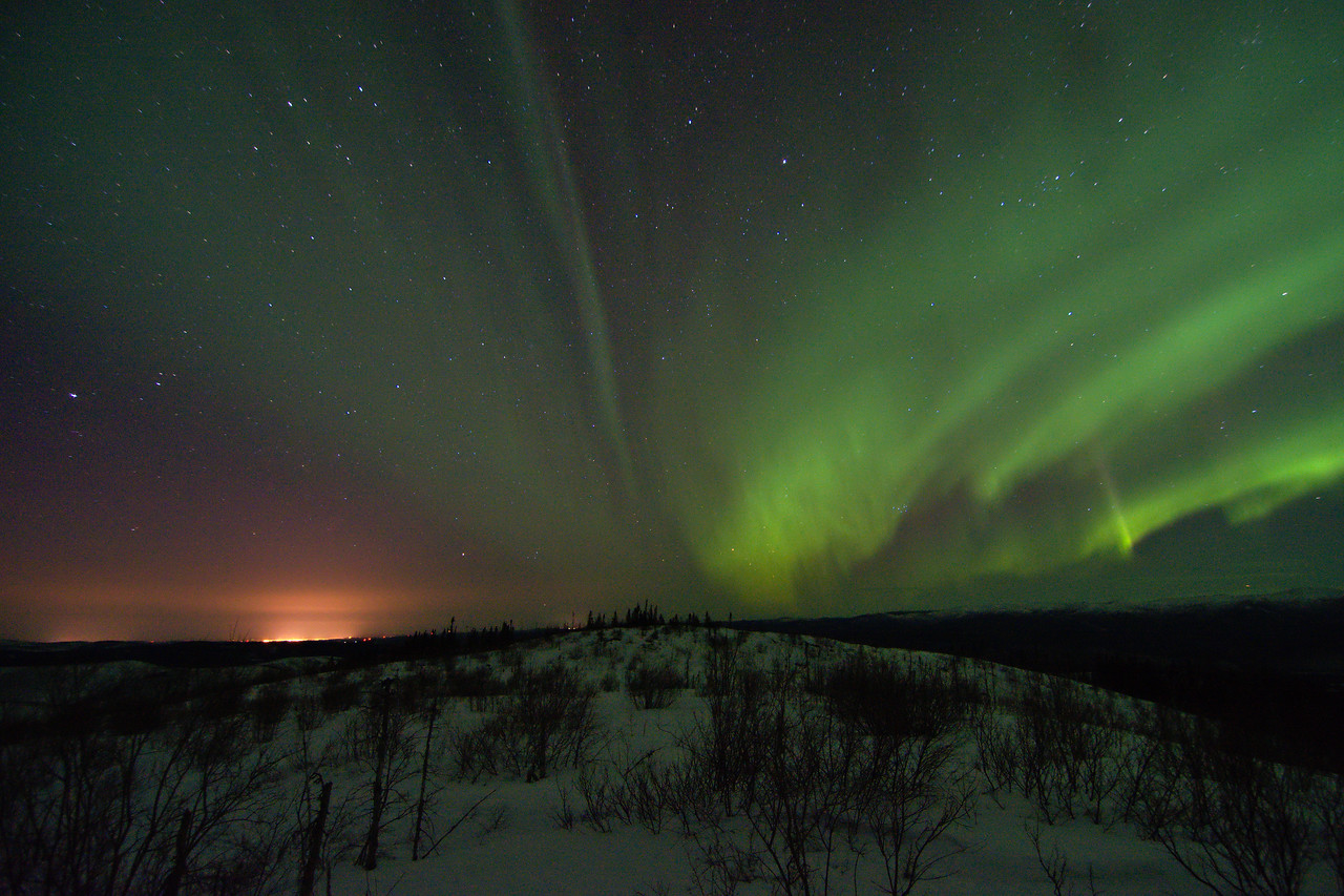 Green northern lights with Fairbanks city lights in the distance