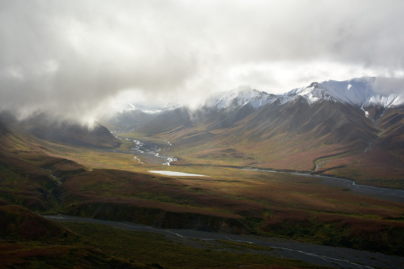 Sunlight punches through low clouds illuminating rivers and kettle ponds in the Eielson area of Denali National Park. Taken from the Eielson Alpine Trail.