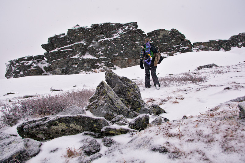 A hiker nears rock outcroppings in the snow below the summit of Wickersham Dome