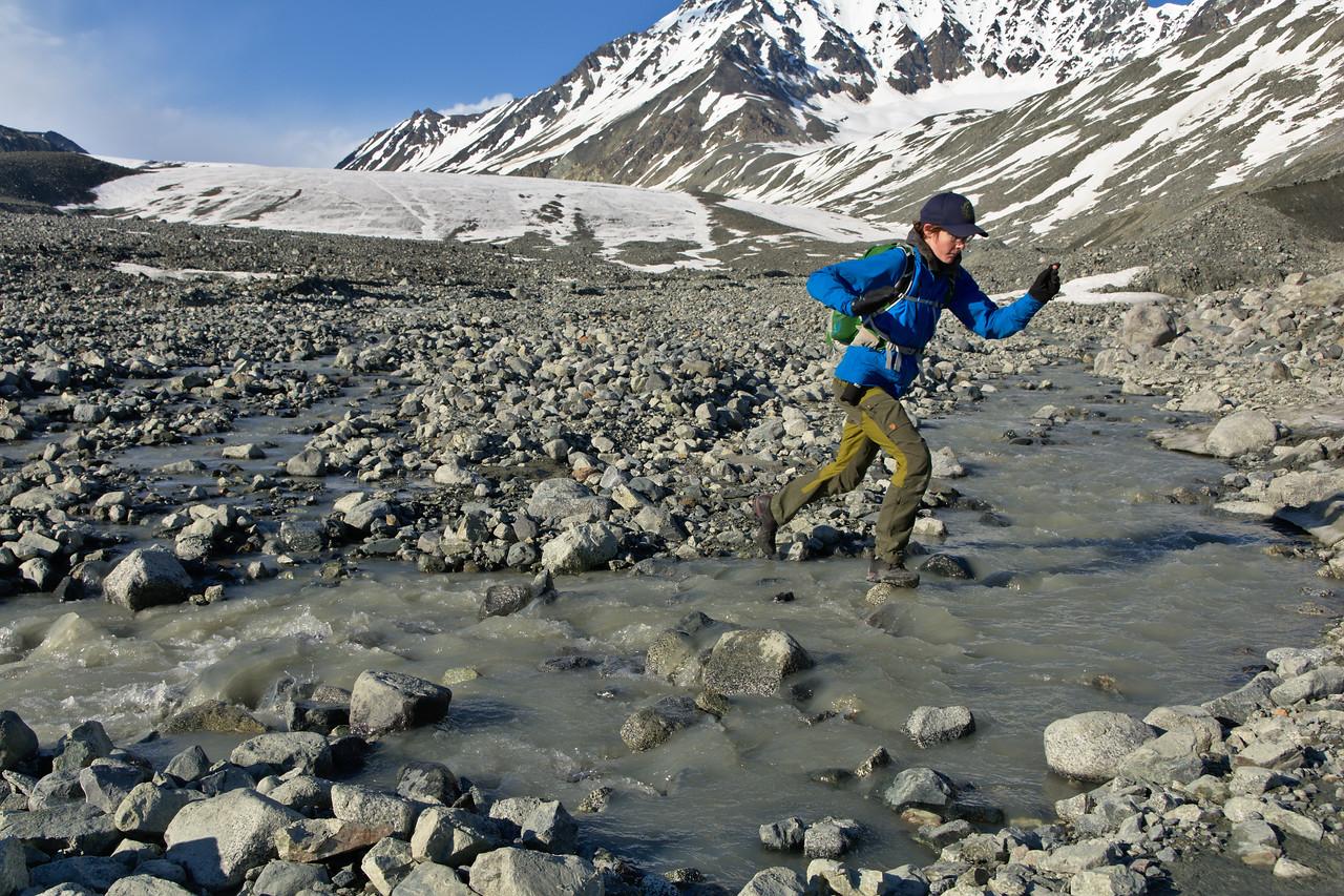 A hiker crossing streams to get to the Gulkana Glacier