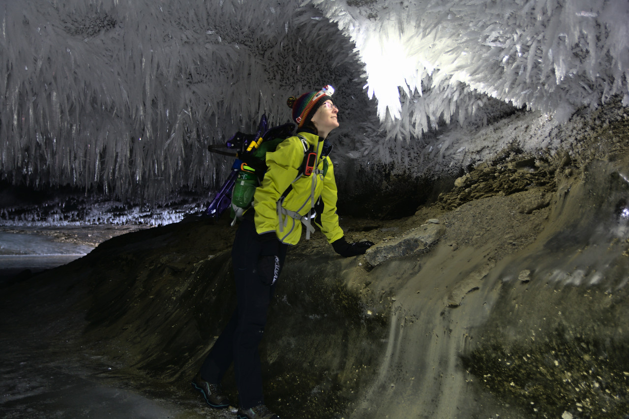 A hiker with a headlamp looking at ice crystals in an glacier cave