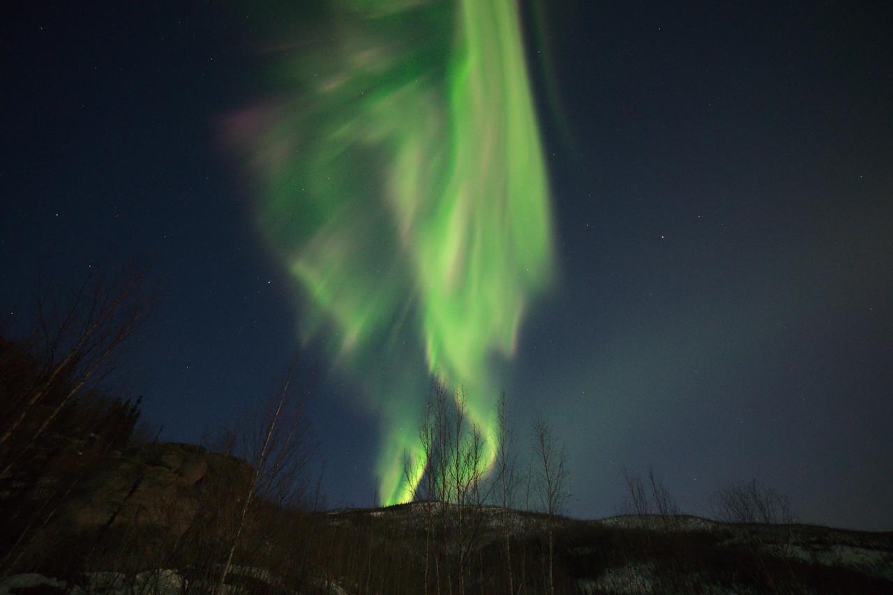 Northern lights erupting over the hills
