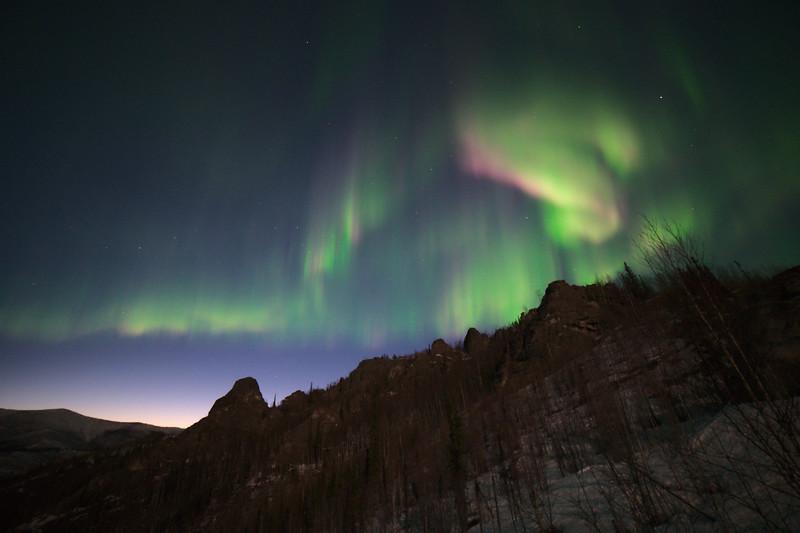 Pink and green northern lights over Angel Rocks near Fairbanks, Alaska