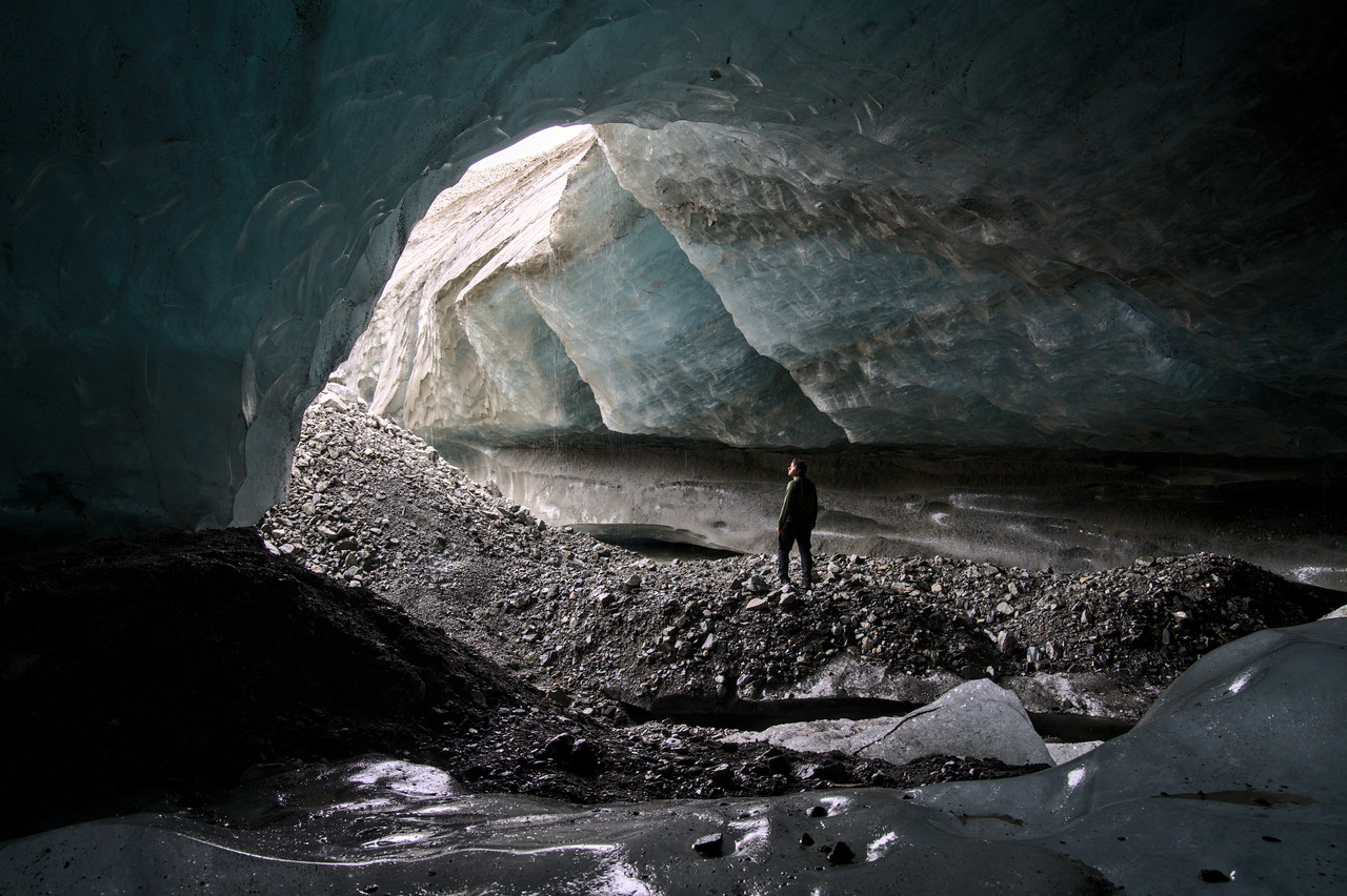 Person standing in the entrance of a glacier cave