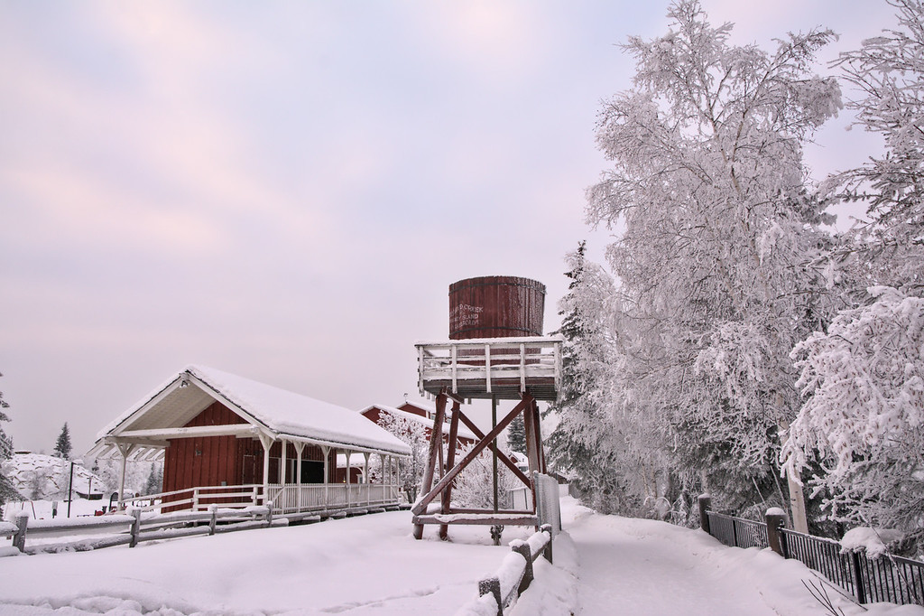 A snowy red water tower and train station at pioneer park