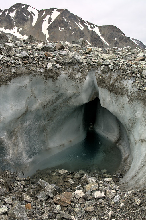 A hole in a glacier with a small pool