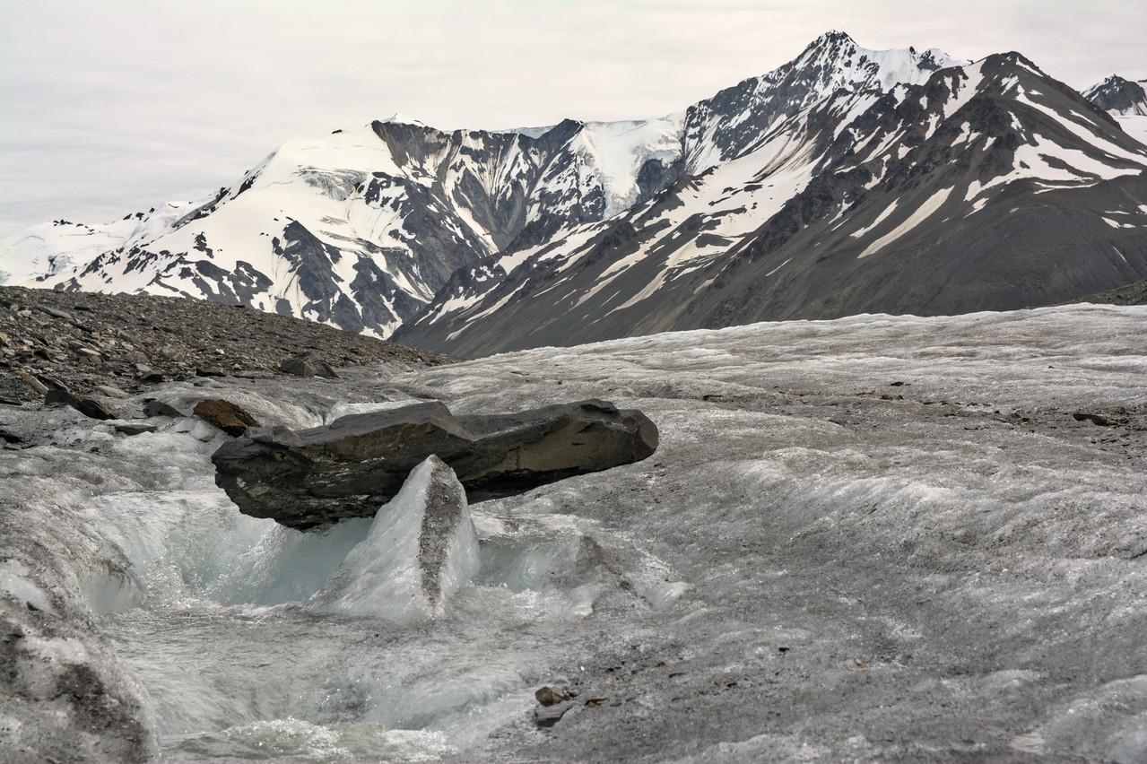 rock balancing over a glacier stream