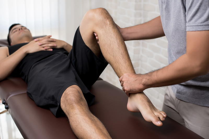 Therapist,Treating,Injured,Leg,Of,Athlete,Male,Patient,In,Clinic