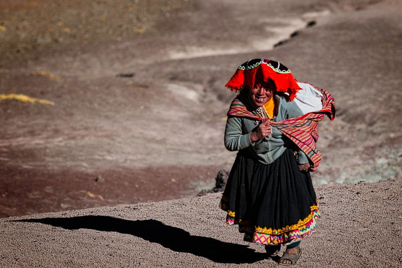 Peruvian Woman climbing the side of the mountain