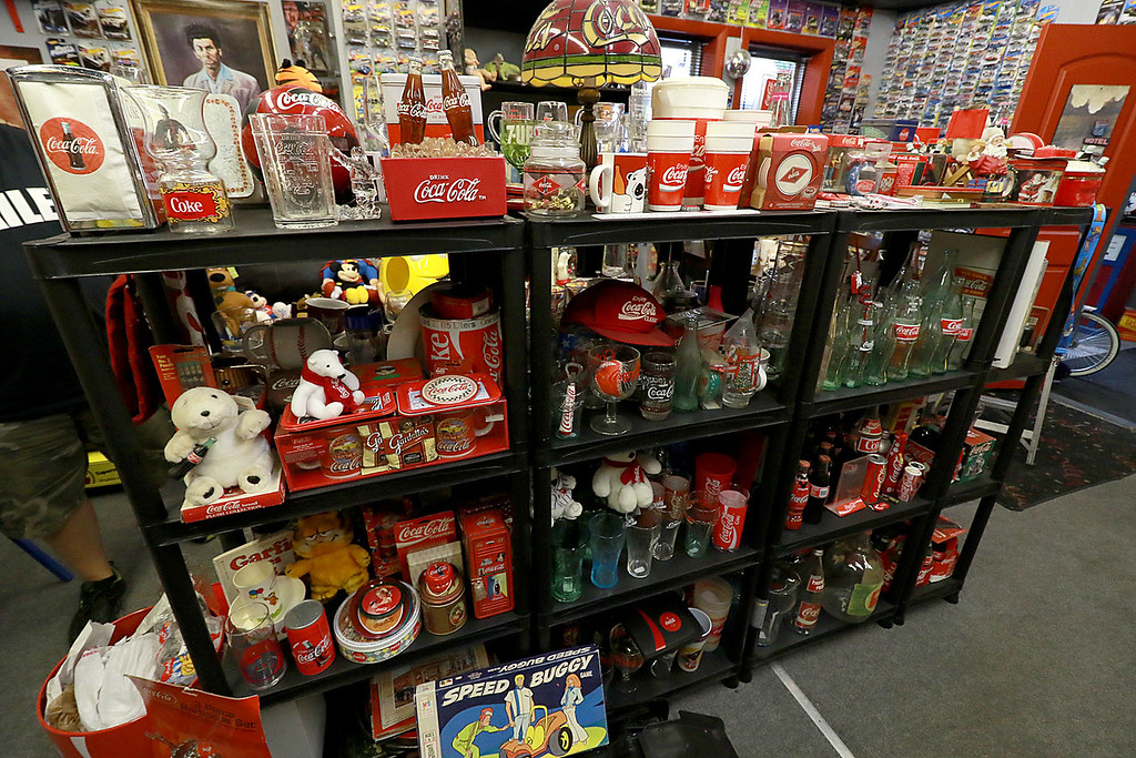 . Dave LaPlante owner of Big D\'s Auto Detailing in Fitchburg likes cars but also has a love for vintage toy\'s. At his shop in Fitchburg in a back room is where he keep many of the toys he has collected. These shelves in his back room are filled with Coca-Cola stuff. SENTINEL & ENTERPRISE/JOHN LOVE